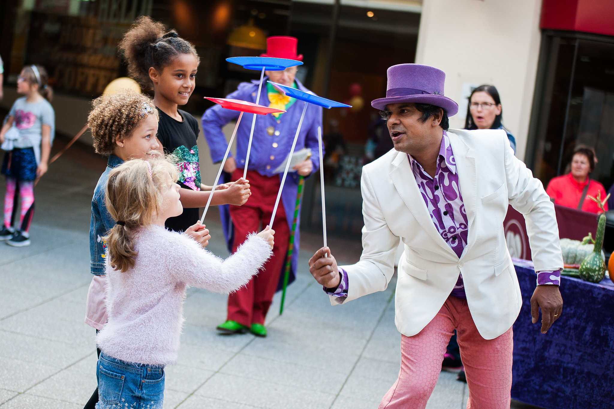Male entertainer spinning plates with children
