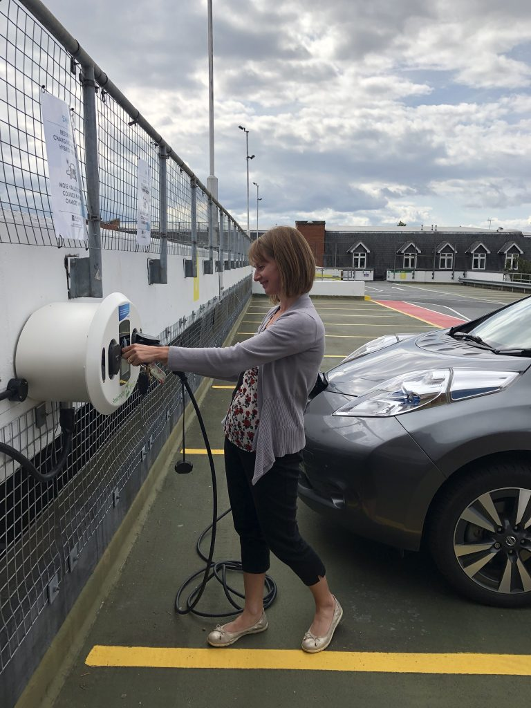 Female Charging Car at Electric Charging Point