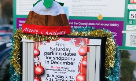 parking machine with poster displaying free parking dates and festive decorations